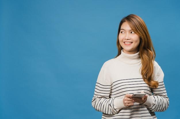 Jovem senhora asiática usando telefone com expressão positiva, sorri amplamente, vestida com roupas casuais, sentindo felicidade e parada isolada na parede azul