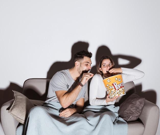 Jovem senhora assistindo tv e comendo pipoca perto de cara no sofá