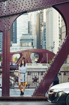 Jovem senhora atravessando a ponte da cidade