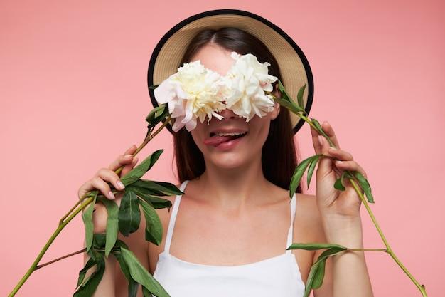 Jovem senhora bonita, com longos cabelos castanhos. usando chapéu e vestido branco. segurando flores sobre os olhos e mostrando a língua, aparência boba. fique isolado sobre uma parede rosa pastel