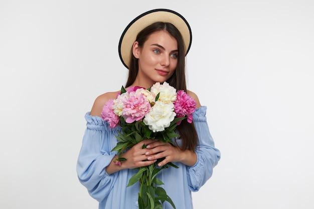 Jovem senhora bonita, com longos cabelos castanhos. usando um chapéu e um lindo vestido azul. segurando um buquê de lindas flores. observando à direita no espaço da cópia sobre a parede branca