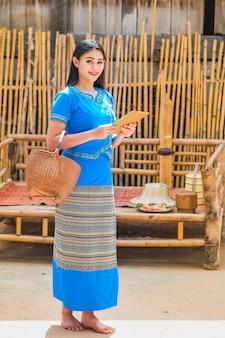Jovem senhora bonita em um vestido tailandês tradicional com uma tabuleta para receber pedidos do cliente.