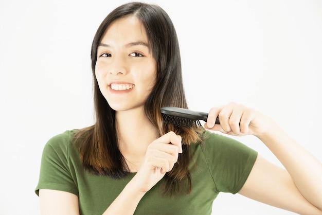 Jovem senhora bonita feliz usando o pente para reta seu cabelo - conceito de cuidado de cabelo de beleza de mulher