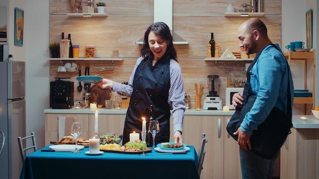 Jovem senhora caucasiana cozinhando para o jantar romântico do marido, esperando na cozinha. mulher preparando jantar festivo com comida saudável, homem voltando do trabalho surpreso beijando e abraçando sua esposa