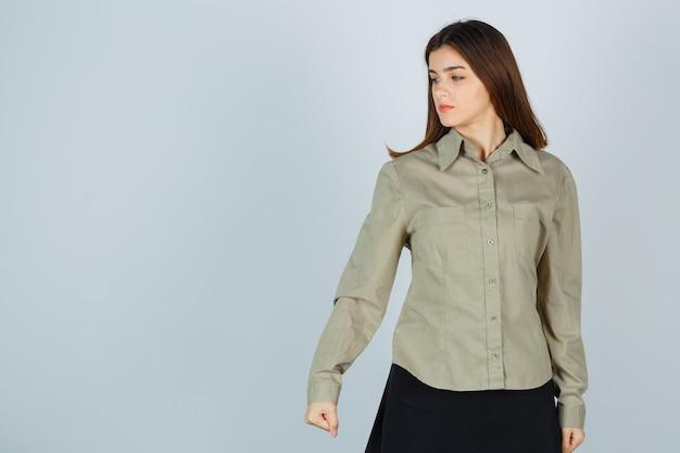 Jovem senhora cerrando o punho com raiva enquanto olha para baixo na camisa, saia e parece ofendida, vista frontal.