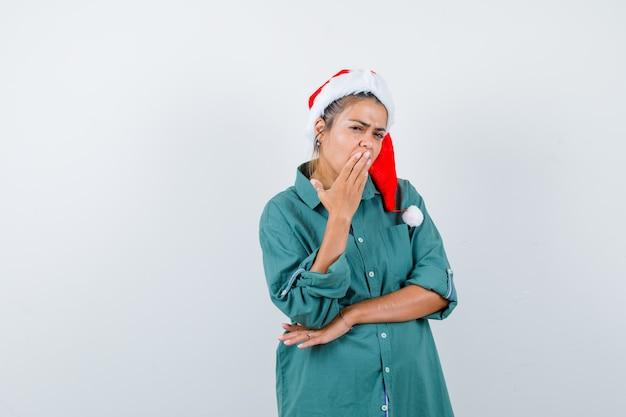Jovem senhora com a mão na boca com chapéu de natal, camisa e olhando pensativa, vista frontal.