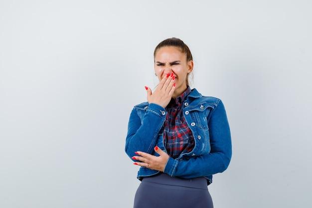 Jovem senhora com a mão na boca em uma camisa, jaqueta e olhando triste, vista frontal.