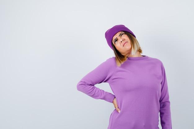 Jovem senhora com a mão na cintura em um suéter roxo, gorro e parecendo dolorido. vista frontal.