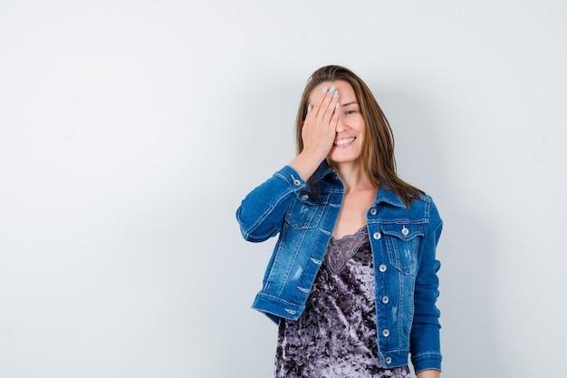 Jovem senhora com a mão no olho na blusa, jaqueta jeans e olhando alegre, vista frontal.