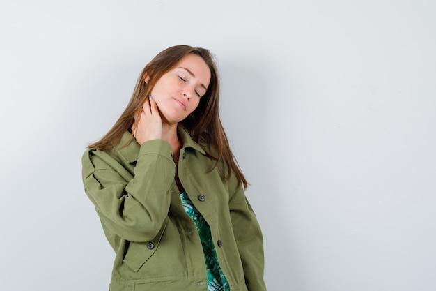Jovem senhora com a mão no pescoço em jaqueta verde e parecendo cansada, vista frontal.