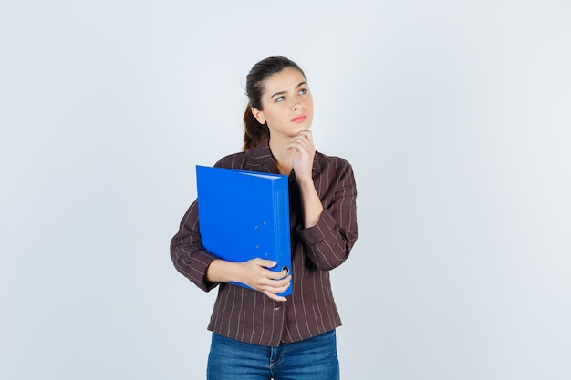 Jovem senhora com a mão no queixo em camisa, jeans e olhando melancólica, vista frontal.