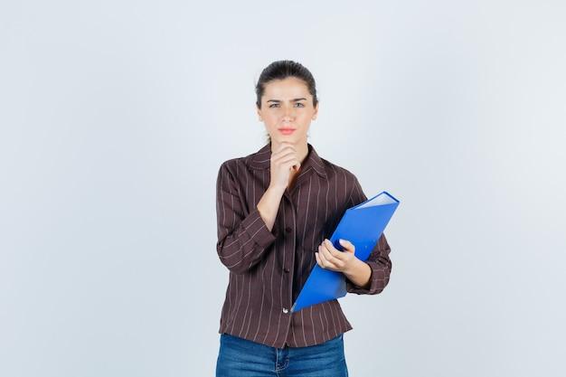 Jovem senhora com a mão no queixo em camiseta, jeans e olhando pensativa, vista frontal.
