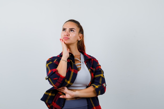 Jovem senhora com a mão no queixo por cima, camisa xadrez e olhando pensativa. vista frontal.