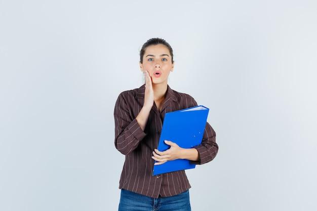 Jovem senhora com a palma da mão na bochecha em camisa, jeans e parecendo chocada, vista frontal.