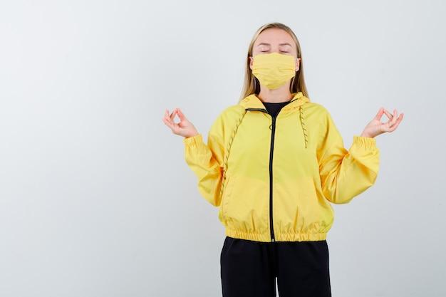 Jovem senhora com agasalho, máscara mostrando gesto de ioga com os olhos fechados e olhando relaxado, vista frontal.