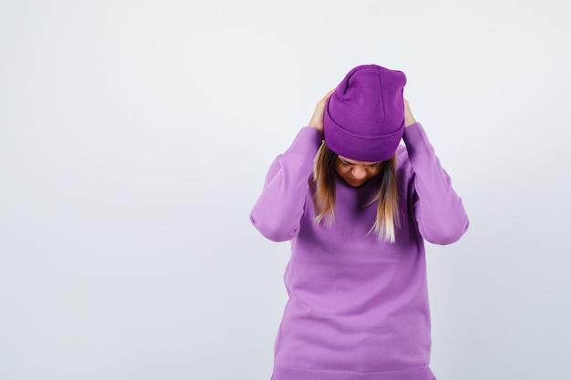Jovem senhora com as mãos atrás da cabeça num suéter roxo, gorro e parecendo cansado. vista frontal.