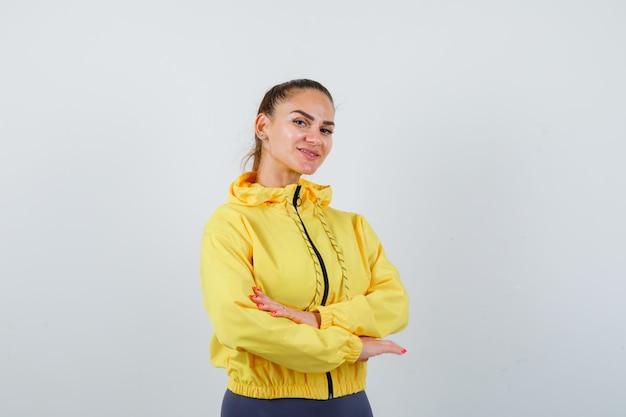 Jovem senhora com as mãos cruzadas na jaqueta amarela e parecendo confiante. vista frontal.