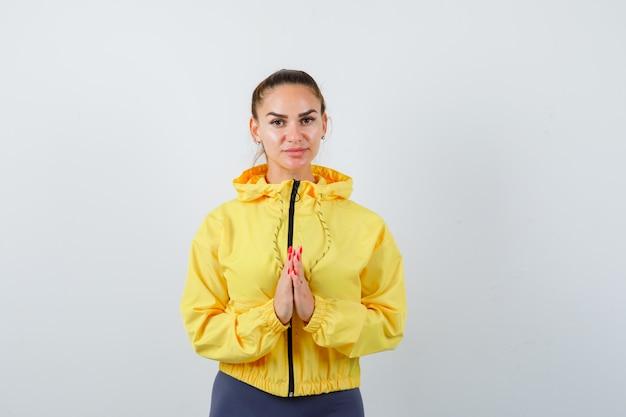 Jovem senhora com as mãos em gesto de oração na jaqueta amarela e olhando em paz, vista frontal.