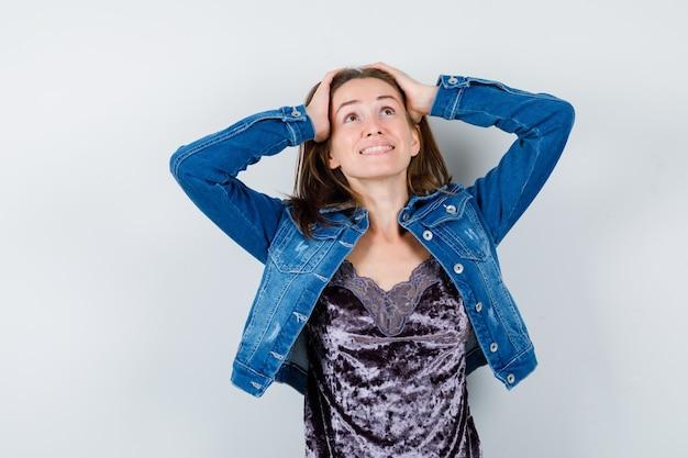 Jovem senhora com as mãos na cabeça enquanto olha para cima na blusa, jaqueta jeans e parece feliz. vista frontal.