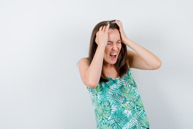 Jovem senhora com as mãos na cabeça na blusa e parecendo irritada, vista frontal.