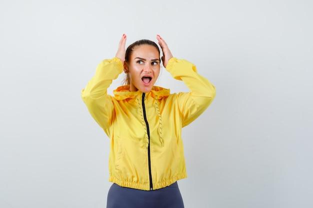 Jovem senhora com as mãos perto da cabeça, abrindo a boca na jaqueta amarela e parecendo surpresa, vista frontal.
