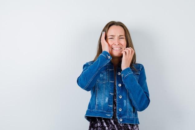 Jovem senhora com as mãos perto do rosto na blusa, jaqueta jeans e olhando melancólica. vista frontal.