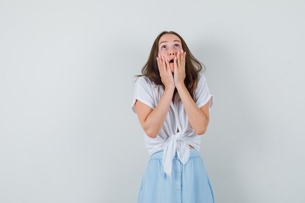 Jovem senhora com blusa branca e saia azul olhando para cima enquanto mantém as mãos no rosto e parece assustada