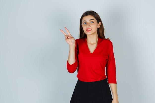 Jovem senhora com blusa vermelha, saia mostrando sinal de vitória e parecendo feliz