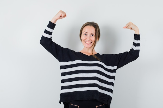 Jovem senhora com camisa casual, mostrando o gesto do vencedor e parecendo feliz