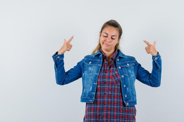 Jovem senhora com camisa, jaqueta, apontando para si mesma e orgulhosa, vista frontal.
