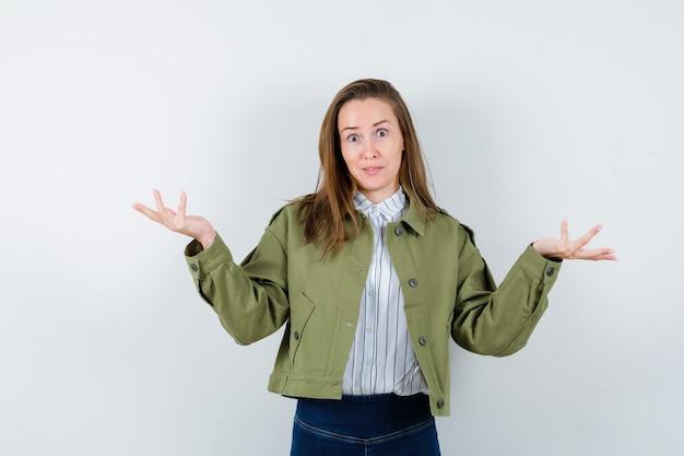 Jovem senhora com camisa, jaqueta, mostrando um gesto de impotência e parecendo confusa, vista frontal.