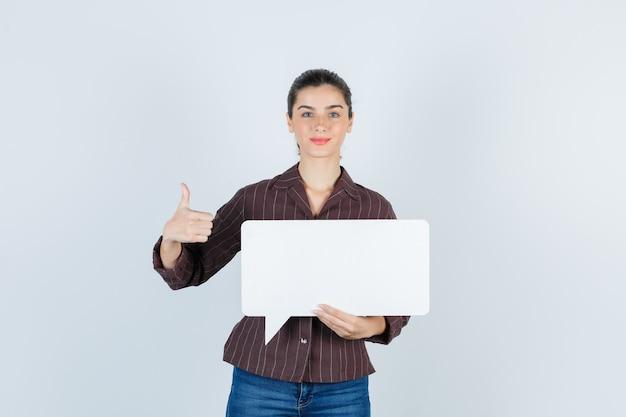 Jovem senhora com camisa, jeans aparecendo o polegar, mantendo o pôster de papel e parecendo satisfeita, vista frontal.