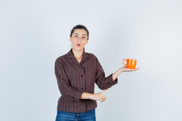 Jovem senhora com camisa, jeans apontando para cima, mantendo a xícara e parecendo chocada, vista frontal.