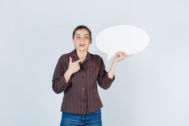 Jovem senhora com camisa, jeans apontando para cima, mantendo o pôster de papel e parecendo chocada, vista frontal.
