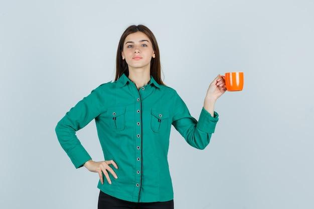 Jovem senhora com camisa, posando, segurando uma xícara de chá laranja e olhando confiante, vista frontal.
