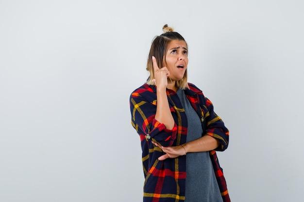 Jovem senhora com camisa xadrez casual apontando para cima, de pé de lado e parecendo pensativa.