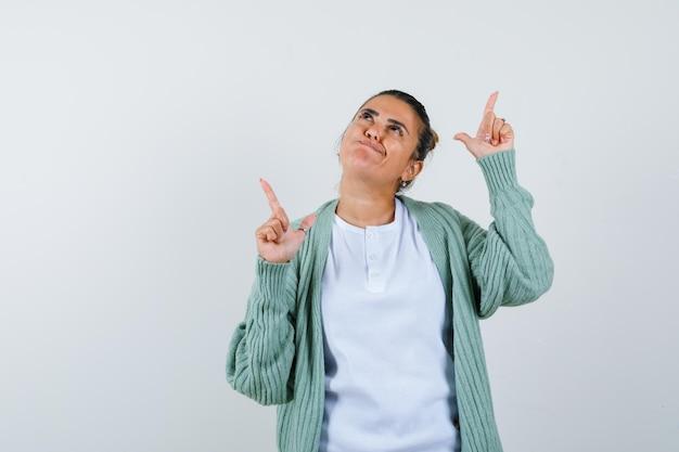 Jovem senhora com camiseta, jaqueta apontando para o lado e parecendo pensativa