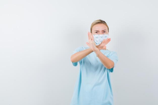 Jovem senhora com camiseta, máscara mostrando gesto de proteção e parecendo autoconfiante isolada