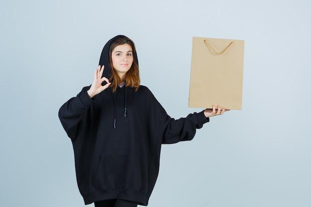 Jovem senhora com capuz enorme, calças mostrando um gesto de ok enquanto segura o pacote e parece confiante, vista frontal.