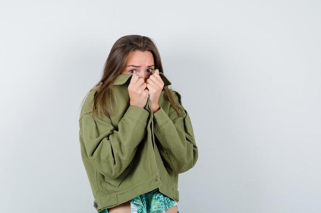 Jovem senhora com casaco verde, escondendo o rosto atrás da gola e parecendo aterrorizada, vista frontal.