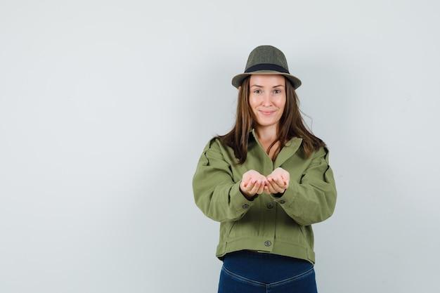 Jovem senhora com chapéu de calça jaqueta esticando as mãos em concha e parecendo gentil