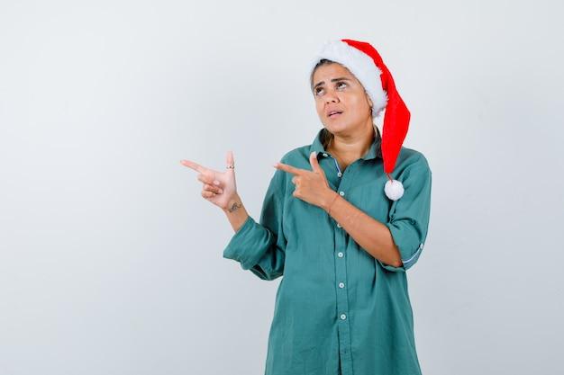 Jovem senhora com chapéu de natal, camisa apontando para o lado esquerdo e olhando ansiosa, vista frontal.