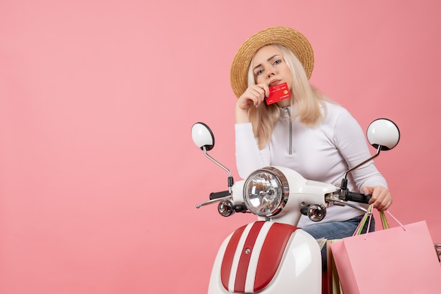 Jovem senhora com chapéu panamá na motocicleta segurando um cartão