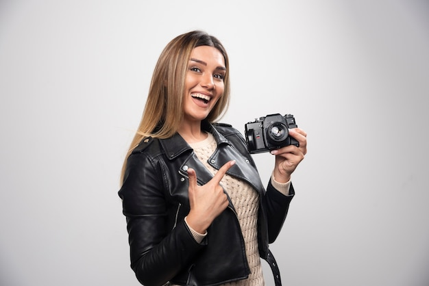 Jovem senhora com jaqueta de couro preta tirando fotos com a câmera de maneira positiva e sorridente
