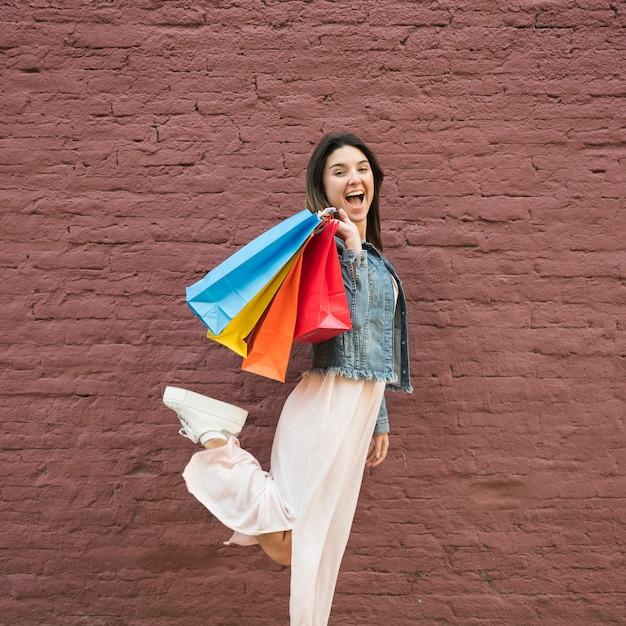 Jovem senhora com muitos sacos de compras brilhantes perto da parede de tijolo