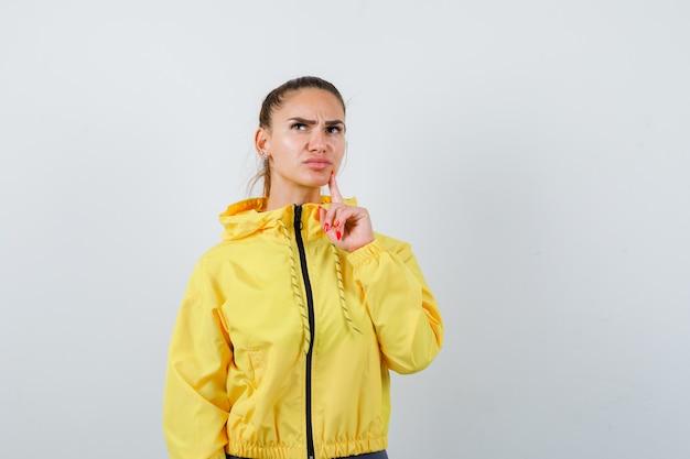 Jovem senhora com o dedo no queixo com jaqueta amarela e olhando pensativa, vista frontal.