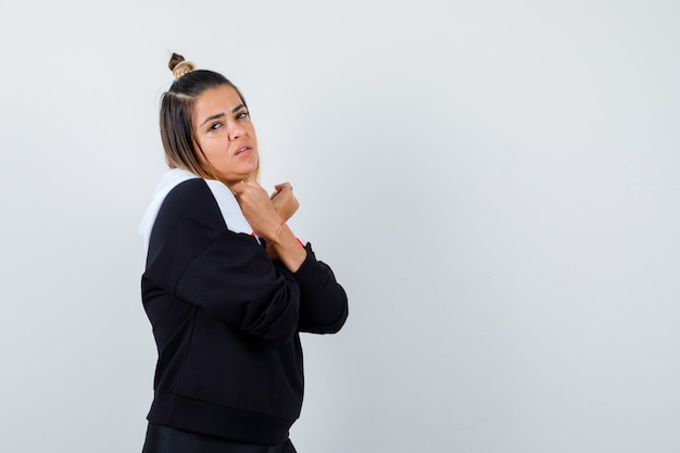 Jovem senhora com suéter com capuz, braços cruzados no peito e aparência atraente