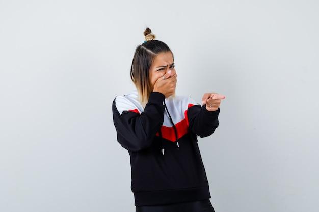 Jovem senhora com suéter com capuz segurando a boca com a mão enquanto aponta para longe e parecendo assustada