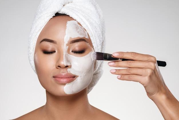 Jovem senhora com toalha na cabeça colocar scrab no rosto isolado