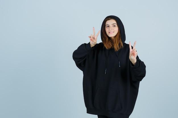 Jovem senhora com um capuz enorme, calças mostrando o sinal da vitória e parecendo com sorte, vista frontal.